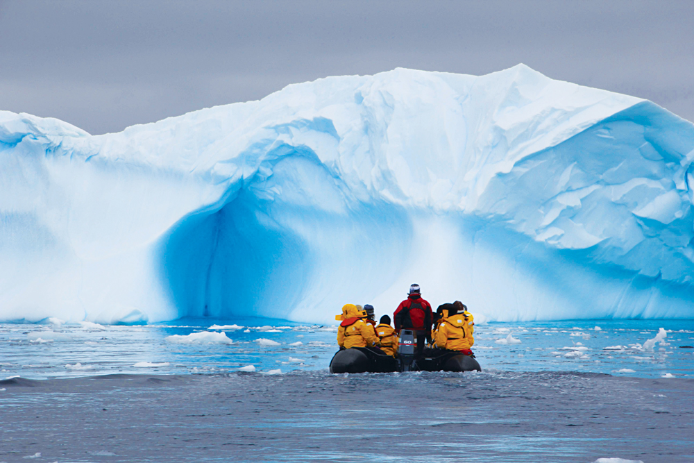 Men on Zodiac witnessing stunning ice formations in Antarctica