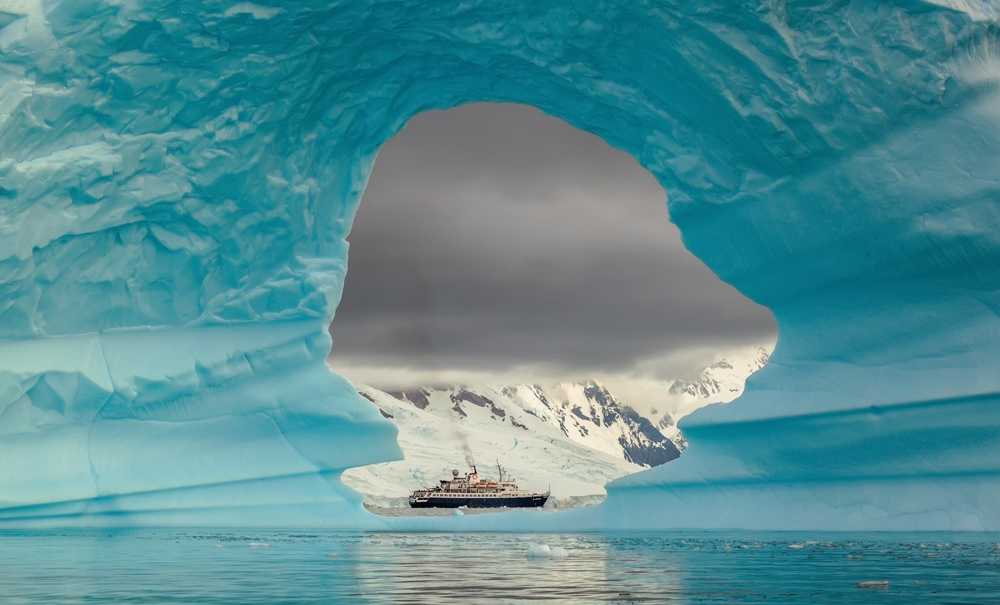 Ship seen through the hole in the iceberg at Antarctic Peninsula, Antarctica
