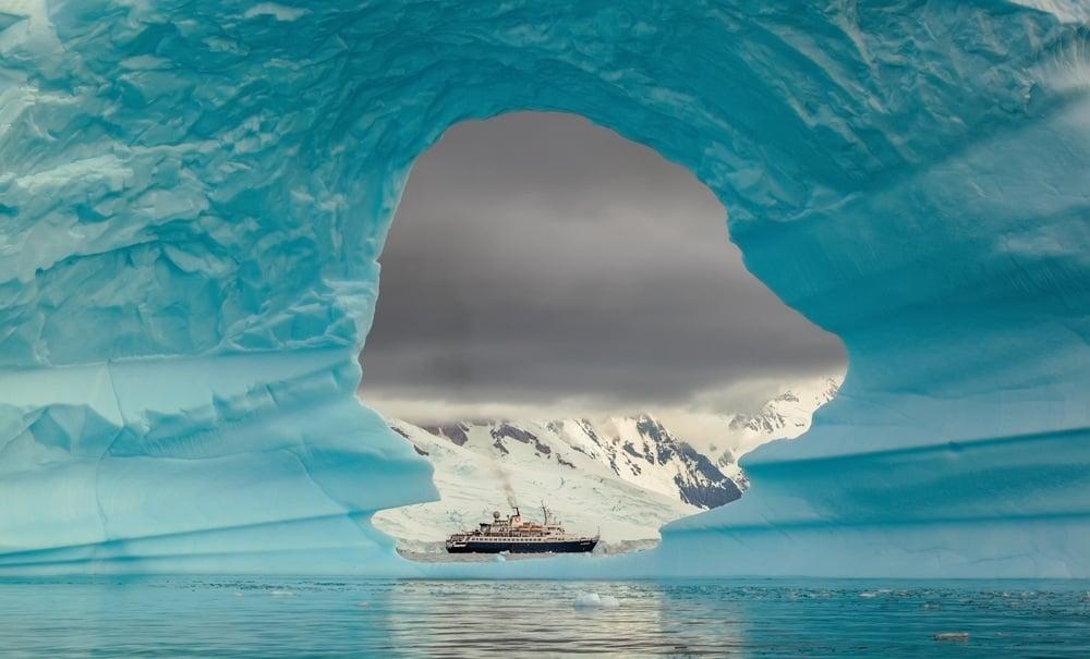 Ship seen through the hole in the iceberg at Antarctic Peninsula, Antarctica
