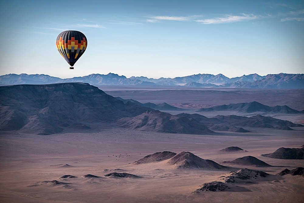 Colourful hot air balloon flying over the high mountains in Namibia