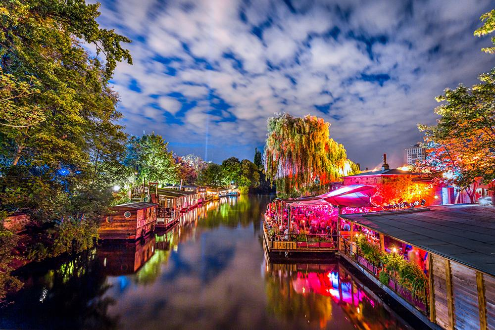 Panoramic view of young people partying in an open-air outdoor club at famous Flutgraben Water Canal, Berlin, Germany