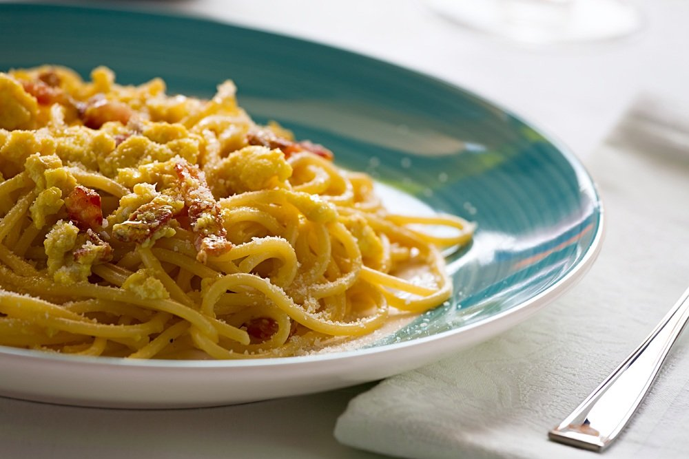 Spaghetti carbonara with egg, smoked bacon and cheese over a table