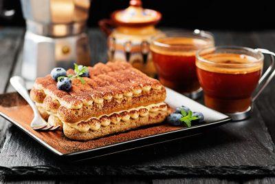 Tiramisu cake with Coffee in Background