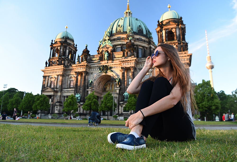 Woman sitting in front of Berlin Cathedral at beautiful sunset, Berlin, Germany