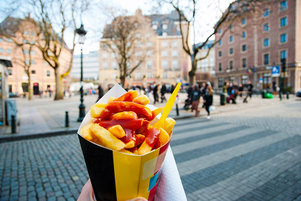 Holding typical Belgian fries in hand in the streets of Brussels, Belgium