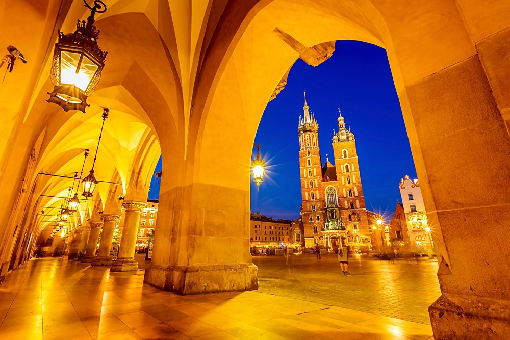 Main square in old town Krakow with St Mary Basilica through arch of Rynek Underground exhibition building, Poland
