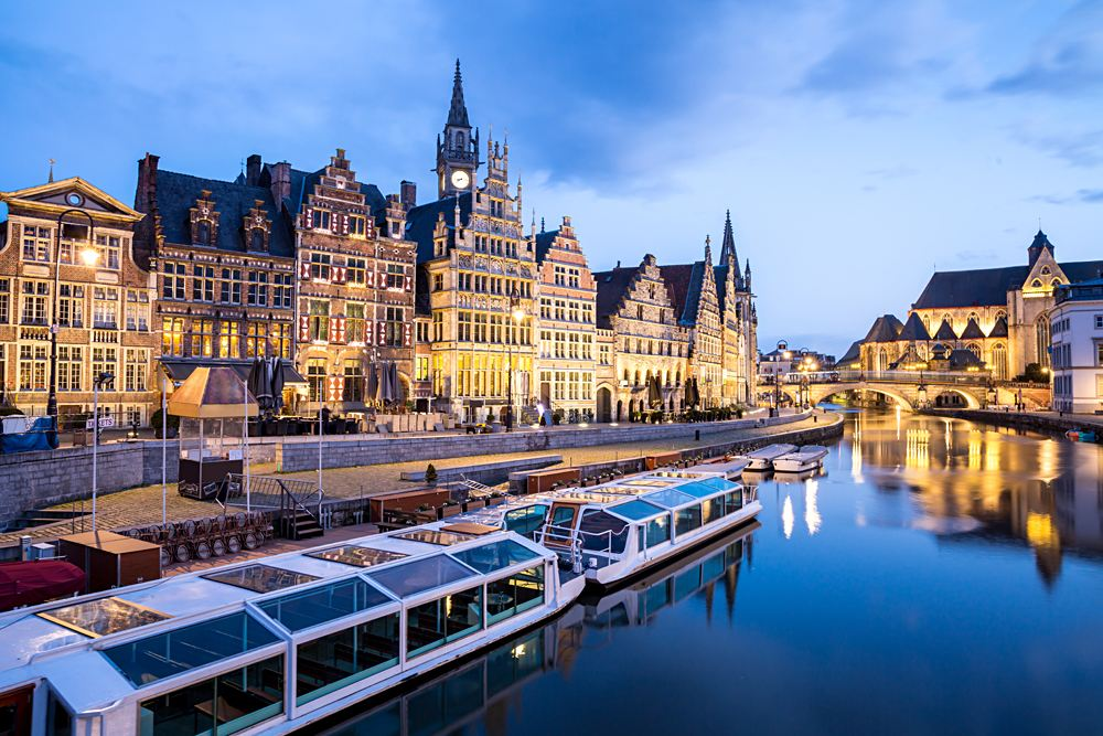 Picturesque medieval buildings at dusk on Leie river in Ghent town, Belgium