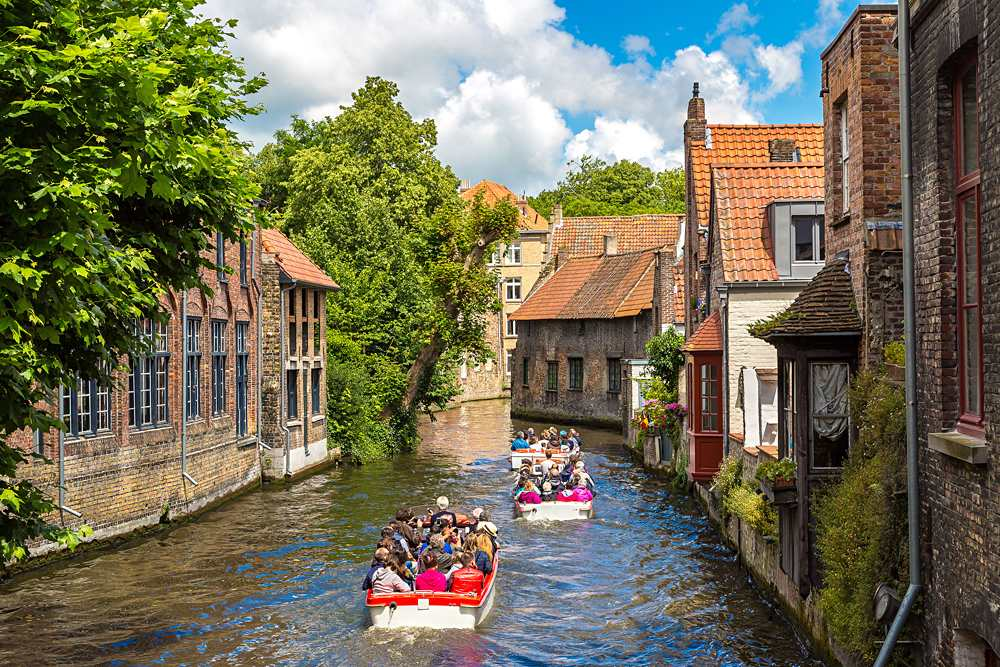 Tourist boat on canal in Bruges on a beautiful summer day, Belgium