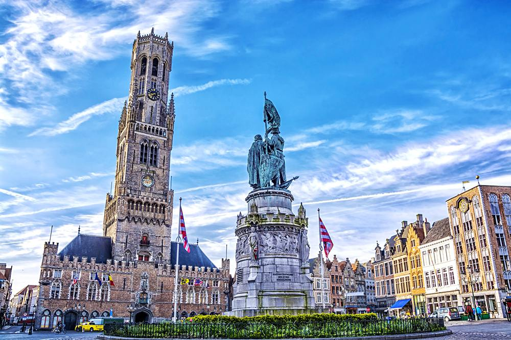 Tower Belfort and colourful old brick house on the Grote Markt square, Bruges, Belgium
