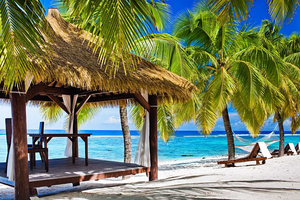 Tropical gazebo with chairs on deserted beach with palm trees, Rarotonga, Cook Islands