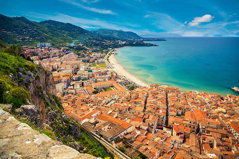 Upper view of bright orange roofs near the sea in Cefalu, Sicily, Italy
