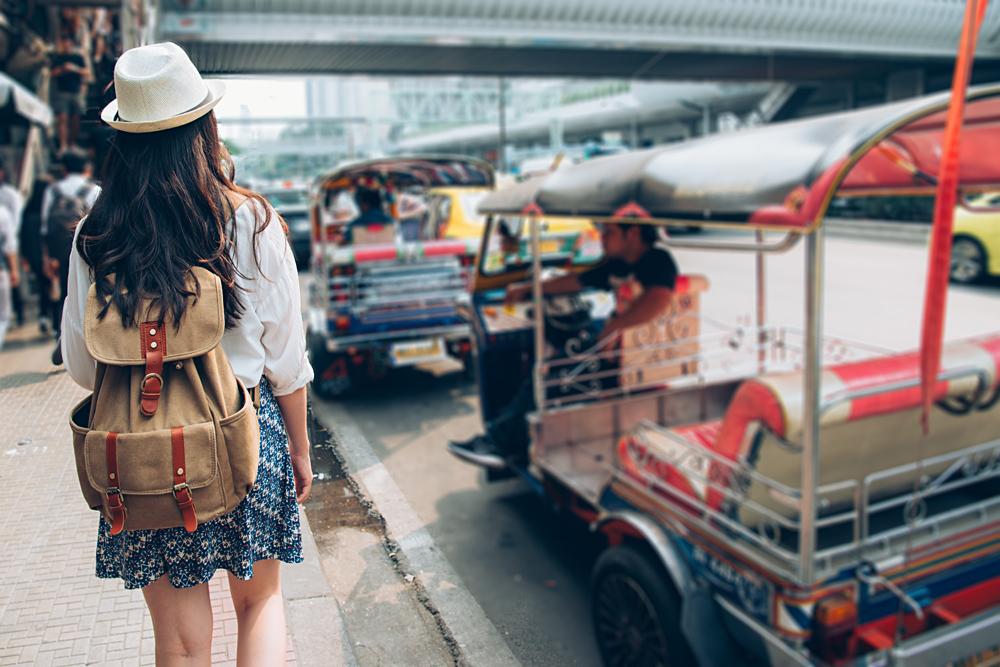 Woman tourist walking on busy Bangkok street, Thailand