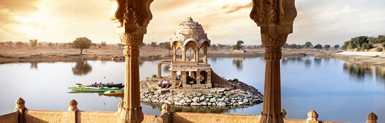 Arches and temple in Gadi Sagar lake at sunset sky in Jaisalmer, Rajasthan, India