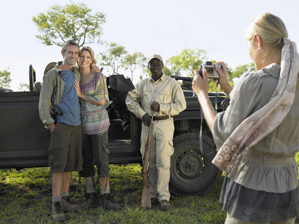 Couple and safari guide posing by jeep, Kruger National Park, South Africa