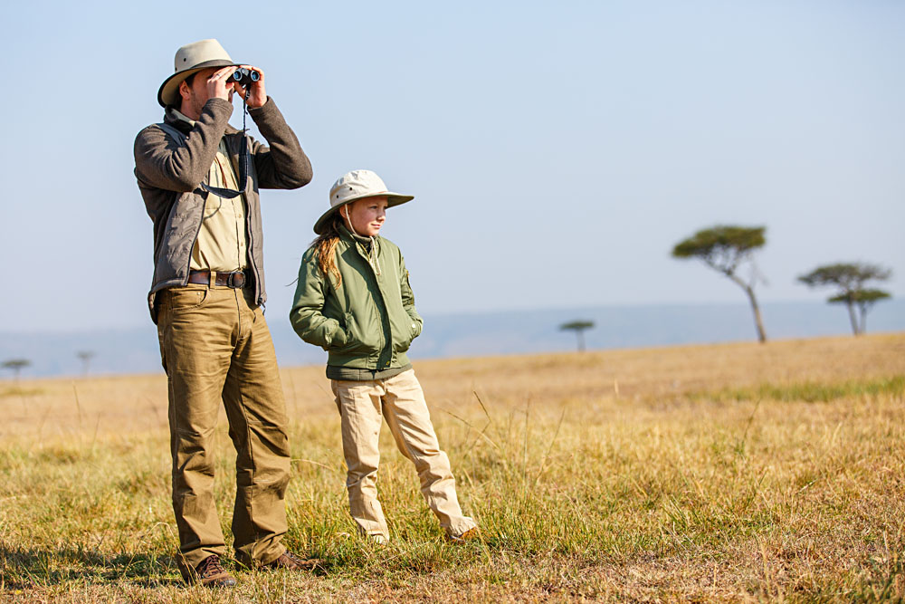 Father and child on African safari vacation enjoying bush view