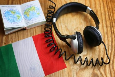 Italian language course headphone and flag on wooden table