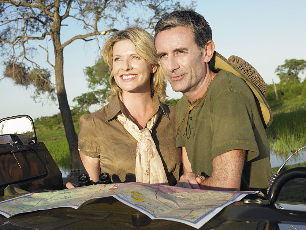 Smiling couple with at map on bonnet of jeep looking at view, Africa safari