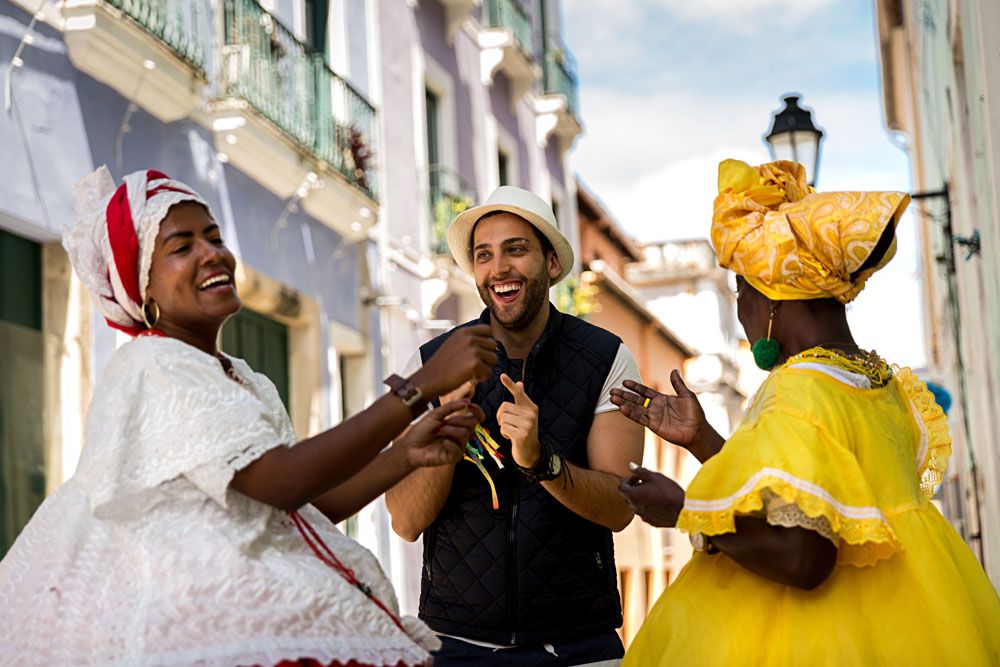 Tourist dancing with local Baianas in Salvador, Bahia, Brazil