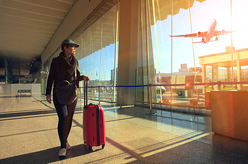 Traveling woman and luggage walking in airport terminal and airplane flying outside