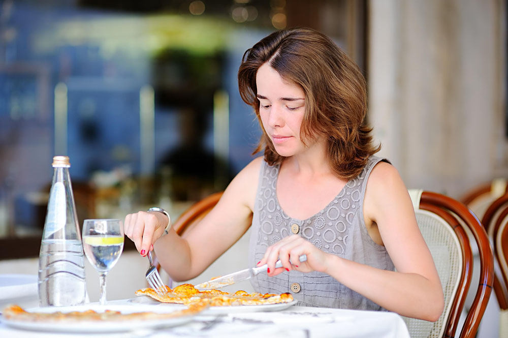 Woman eating traditional italian pizza in outdoors restaurant in Venice, Italy