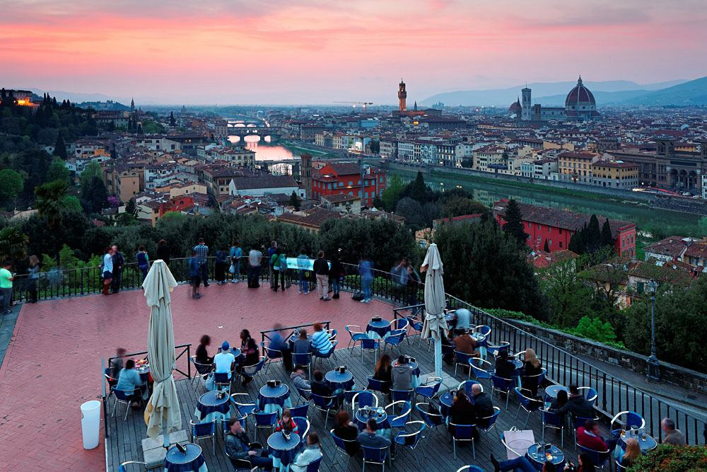 Tourists enjoying a panoramic view of Arno River from Piazzale Michelangelo at Sunset, Florence, Italy