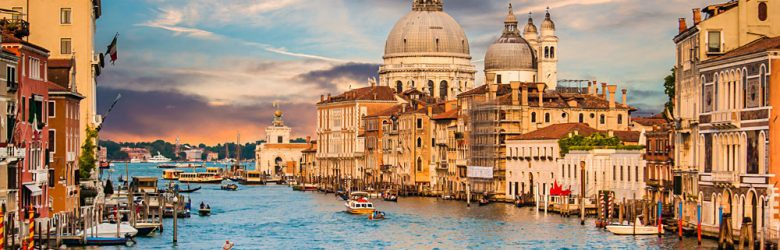 Traditional Gondola on famous Canal Grande with Basilica di Santa Maria della Salute at sunset in Venice, Italy