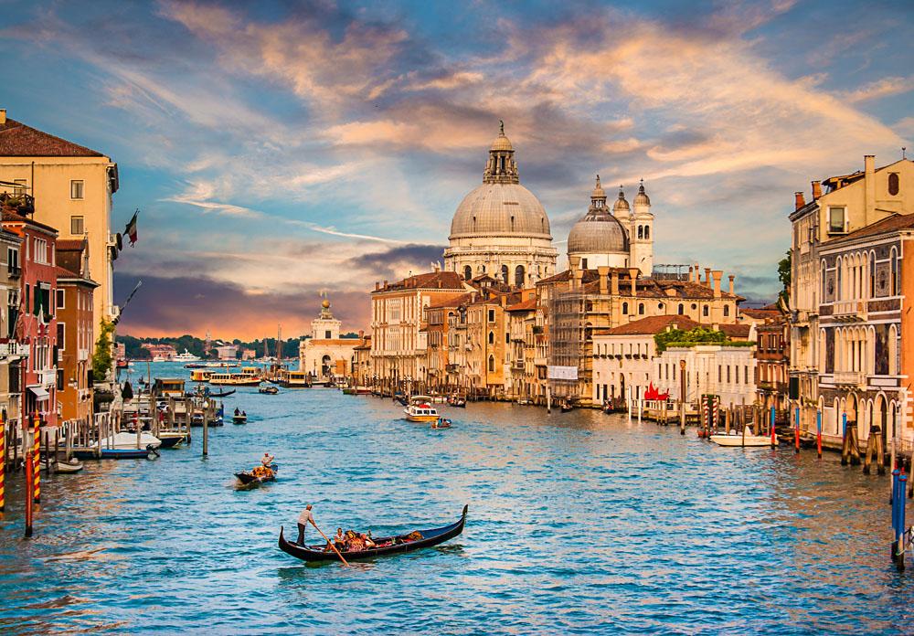 Traditional Gondola on famous Canal Grande with Basilica di Santa Maria della Salute at sunset in Venice, Italy