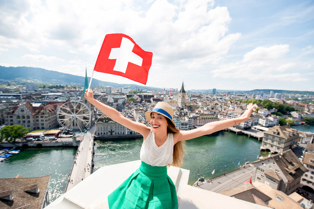 Young female tourist with swiss flag at the top of Grossmunster Tower in Zurich, Switzerland
