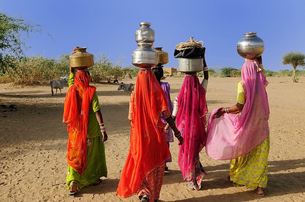Ethnic women going for water in well in Thar Desert near Jaisamler, Rajasthan, India