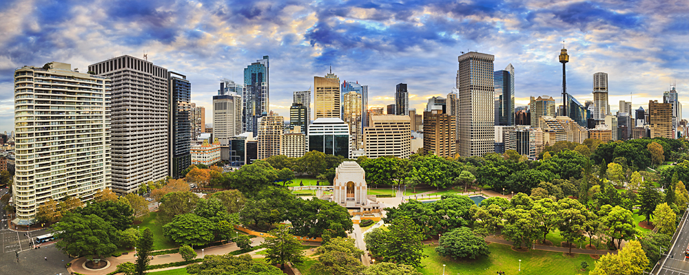 Hyde Park with ANZAC Memorial and CBD cityline on a bright autumn day, Sydney, Australia