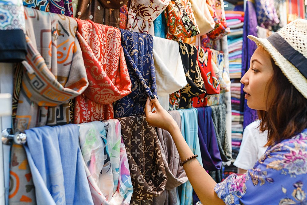 Young Woman Shopping For a Scarf in Bazaar