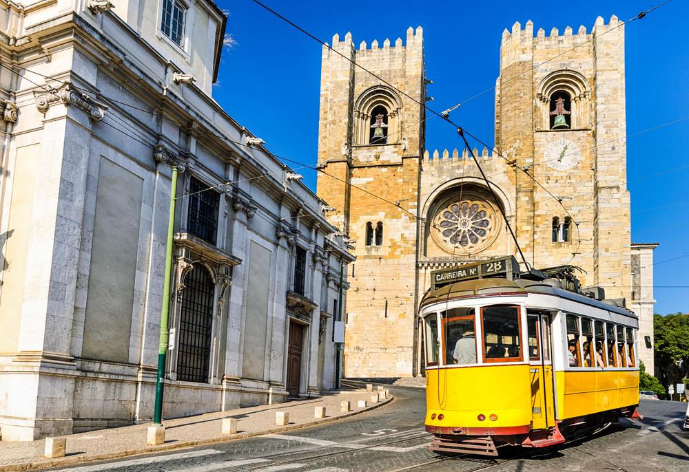 Historic yellow tram in front of the Lisbon Cathedral, Portugal