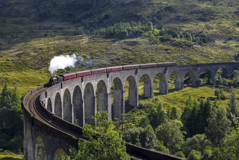 Jacobite steam train on Glenfinnan Viaduct approaching, Highlands, Scotland, UK (United Kingdom)