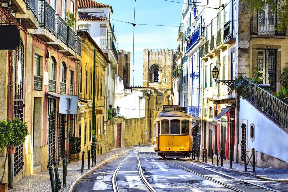 Romantic Lisbon street with the typical yellow tram and Lisbon Cathedral in the background, Portugal
