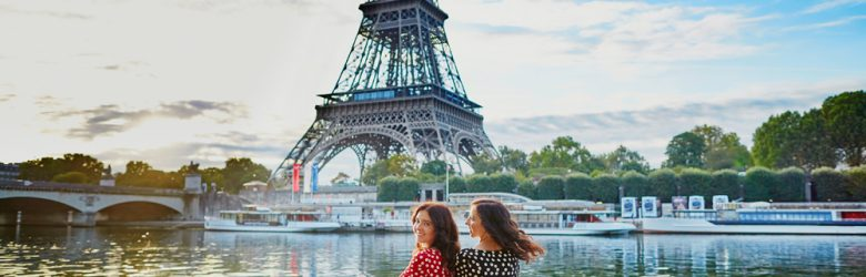 Twin sisters in red and black polka dot dresses in front of the Eiffel tower near the River Seine in Paris, France