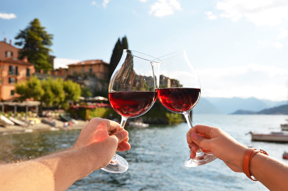 Two wineglasses clinking in Varenna town at Lake Como, Lombardy, Italy