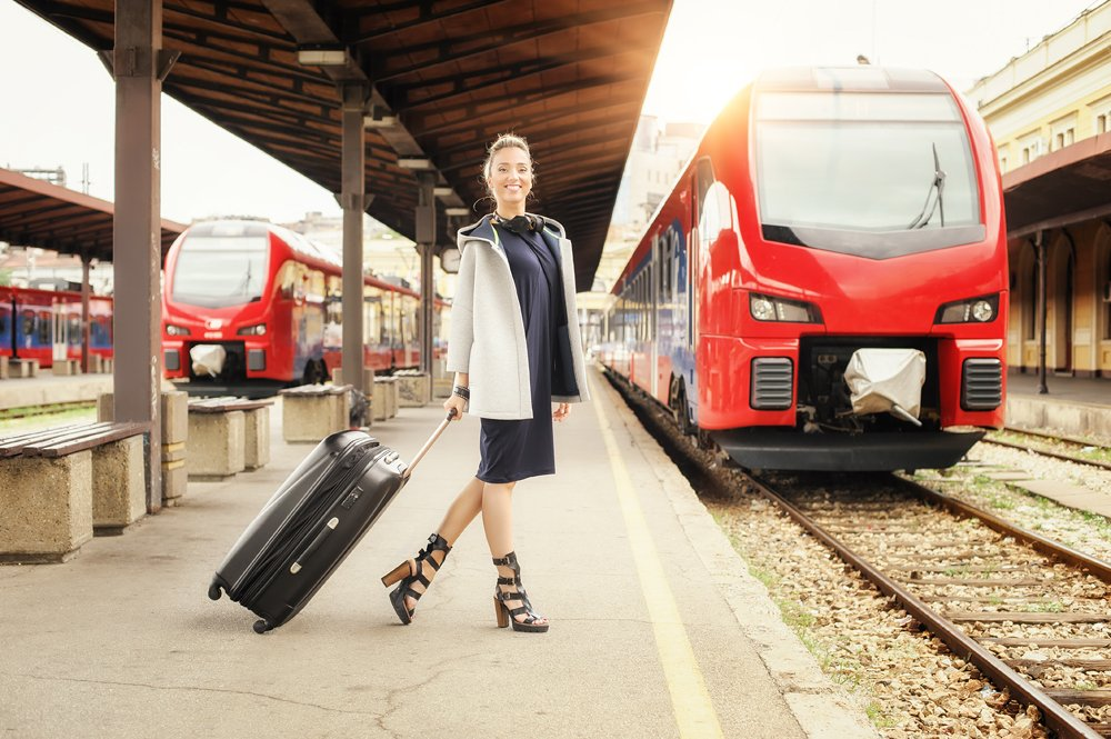Woman with suitcase standing and posing on the railway station