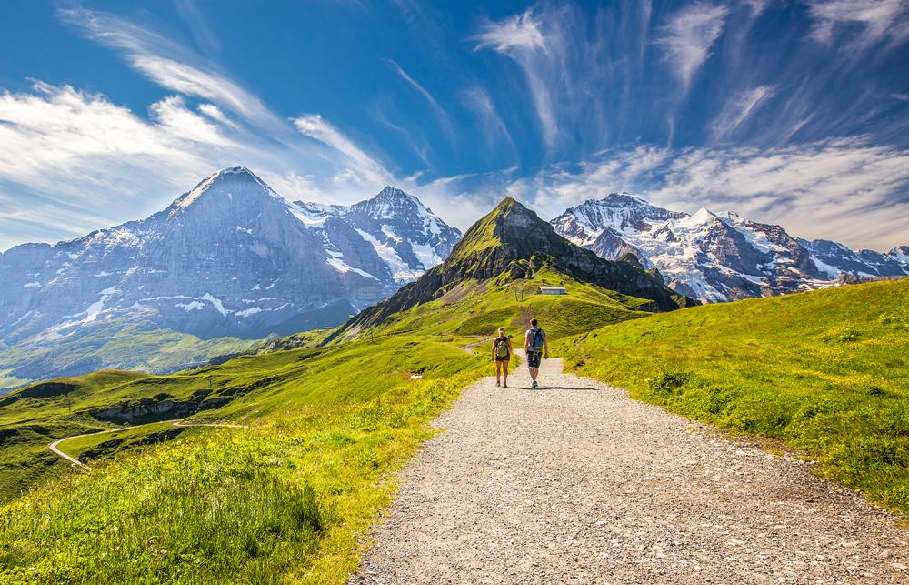 Young couple hiking in trail leading to Kleine Scheidegg from Mannlichen with Swiss Alps in the background, Switzerland