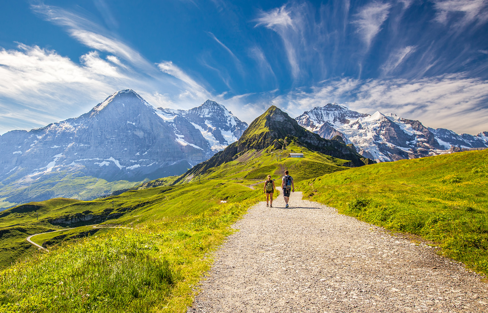 Young couple hiking in trail leading to Kleine Scheidegg from Mannlichen with Swiss Alps in the background, Switzerland