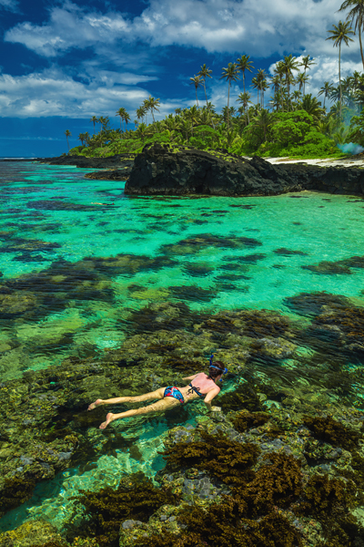 Young woman snorkeling over coral reef on a tropical island with palm trees in Upolu, Samoa