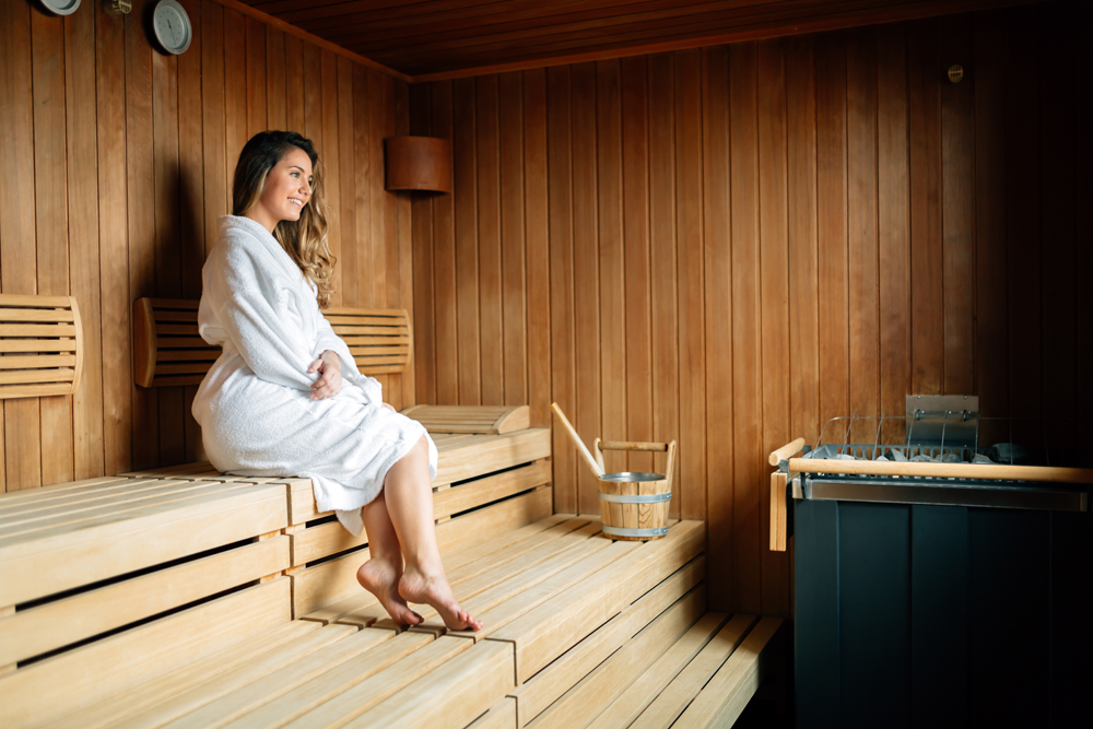 Beautiful woman sitting in Finnish sauna, Finland