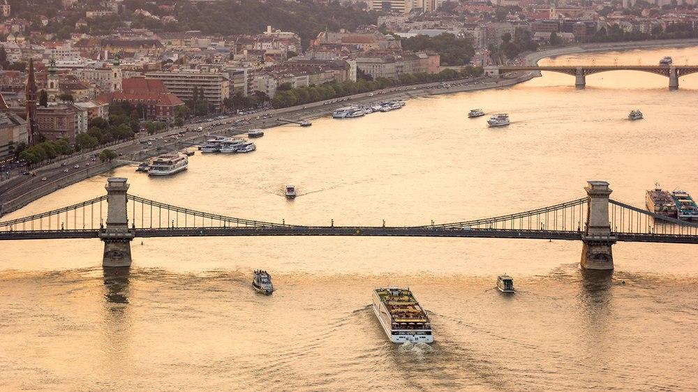 Sightseeing boat tours cruise Danube River under Chain Bridge, Budapest, Hungary
