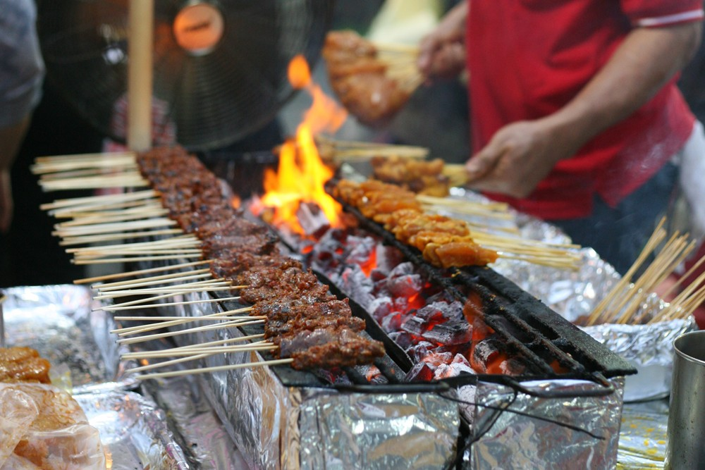Tasty skewers of chicken cooked over hot coals in Singapore's Satay Street food market, Singapore