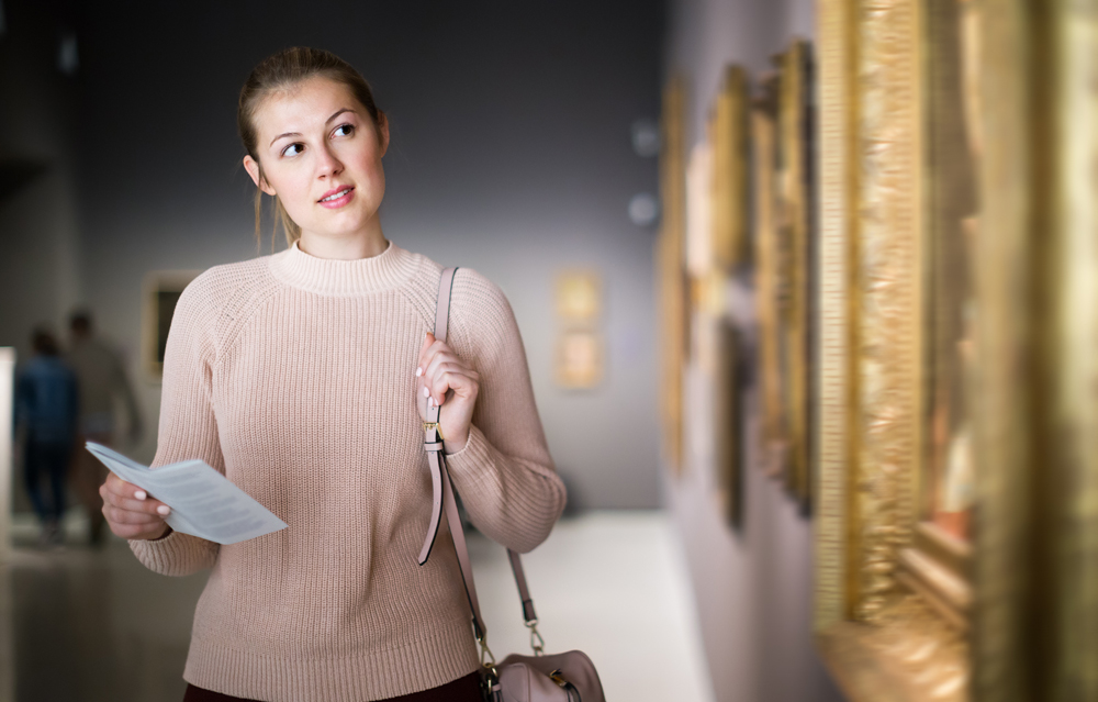 Woman holding guide book standing near pictures in museum of arts