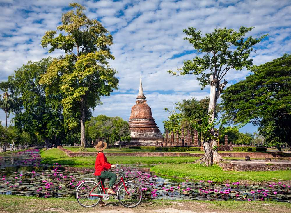 Woman riding bicycle and looking at old Buddhist temple in Sukhothai Historical Park, Thailand