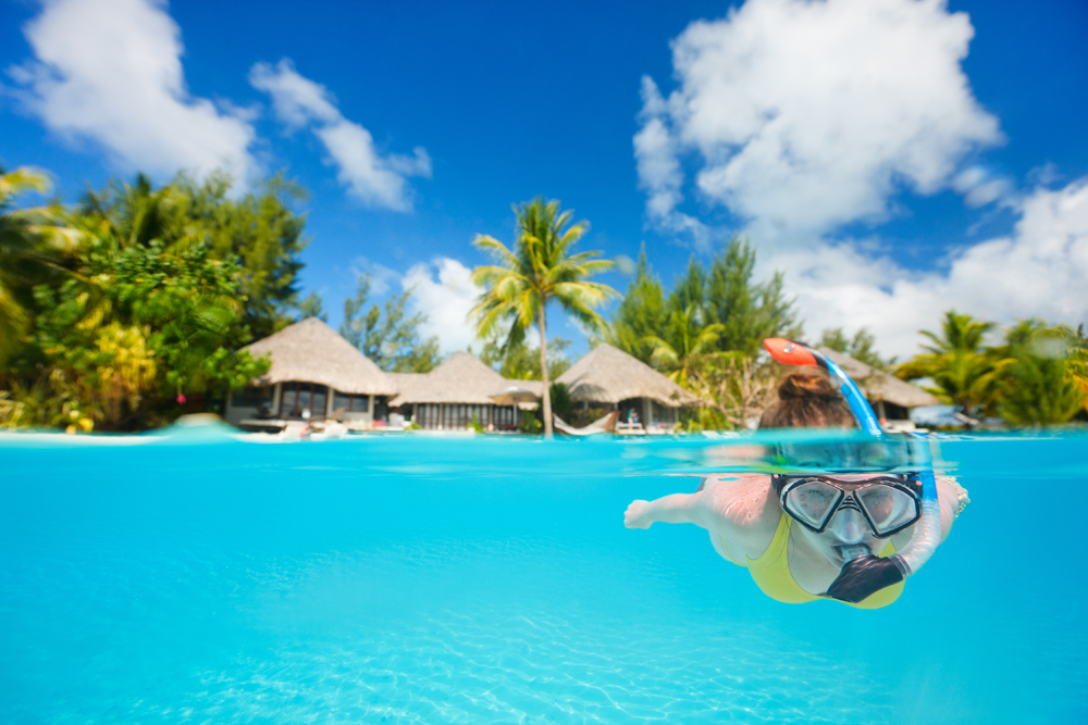 Woman snorkeling in clear tropical waters in front of exotic island, Bora Bora, Tahiti (French Polynesia)