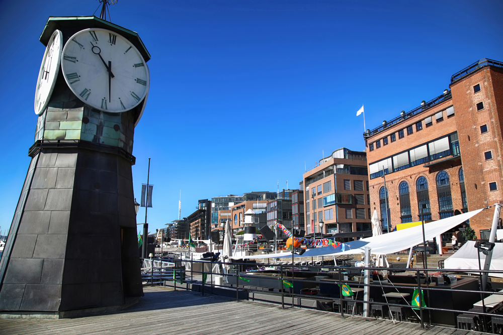 Clock tower on Aker Brygge dock and modern buildings, Oslo, Norway