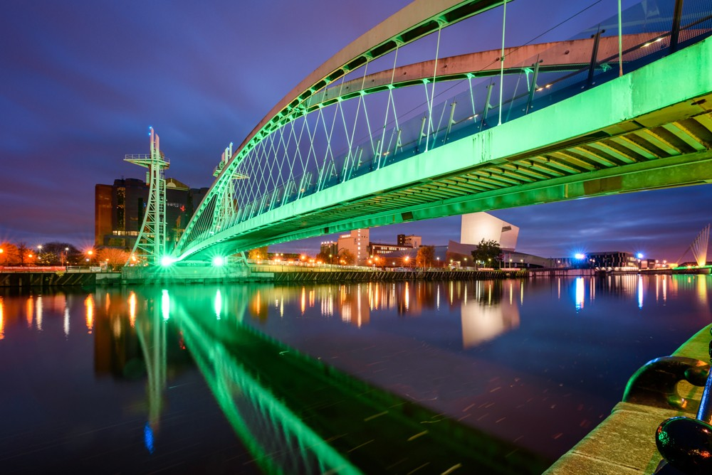 Illuminated Millennium Bridge over the Manchester canal in Salford Quays, Manchester, England, UK