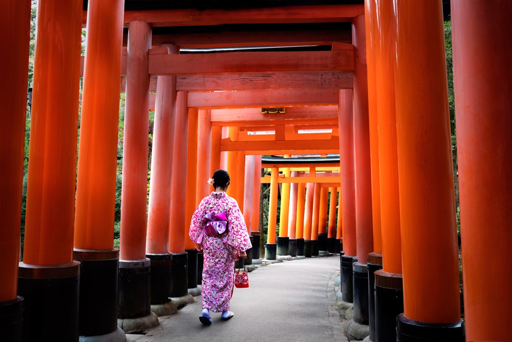 Traditionally dressed woman walking under Tori Gates at the Fushimi-inari Shrine, Kyoto, Japan