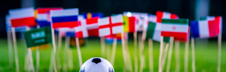 Football ball on green grass and all national flags of FIFA World Cup, Russia 2018